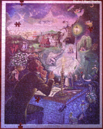 Photo of a jigsaw puzzle (incomplete) of a painting of Hans Christian Anderson and his characters