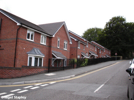 Photo of a row of new houses along the side of a road