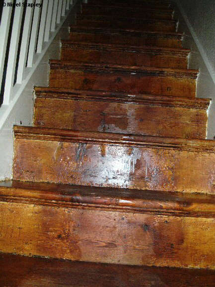 Photo looking up some woodstained stairs